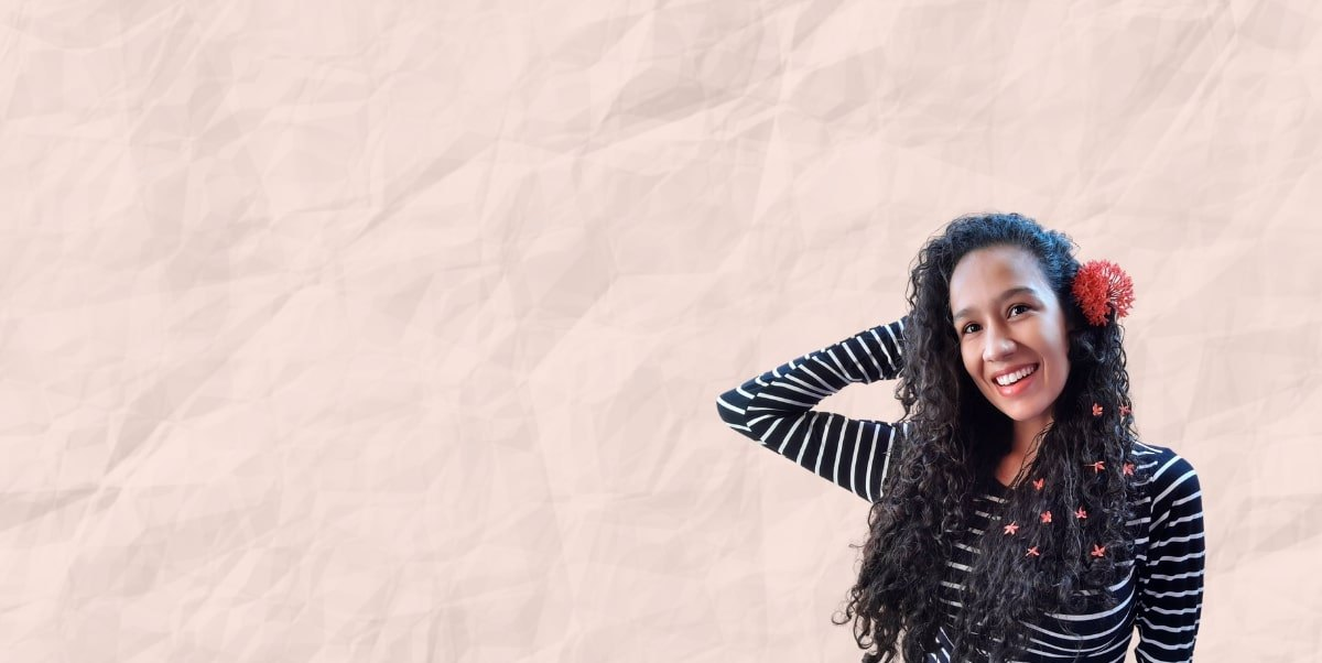 Rose wrinkled paper background with cut out image of curly haired woman smiling into camera